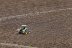 Tractor ploughing agricultural land Royalty Free Stock Image