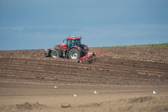 Tractor ploughing agricultural land Royalty Free Stock Images