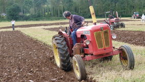 Tractor at a Ploughing Contest in England. Tractor ploughing a straight furrow at a Ploughing match/contest in Devon South West England Royalty Free Stock Photo