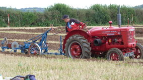 Tractor at a Ploughing Contest in England. Tractor ploughing a straight furrow at a Ploughing match/contest in Devon South West England Stock Image