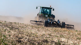 Tractor ploughing on dry field Stock Photos