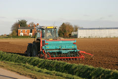 Tractor Ploughing Farm Field. Tractor pulling plough on field with farm house and greenhouse in distance Stock Image
