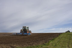 Tractor ploughing field. Scenic view of tractor ploughing field in countryside Stock Photography