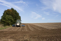 Tractor ploughing field. Scenic view of tractor ploughing field in countryside with blue and cloudscape background Stock Photo