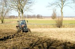 Tractor ploughing field. Scenic view of tractor ploughing furrows in countryside field Stock Photos