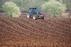 Tractor ploughing field Stock Photos