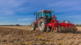 Tractor ploughing field. Field being ploughed by tractor under Blue Sky. Autumn Farming scene in the Netherlands Royalty Free Stock Image
