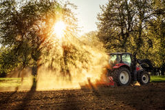 Tractor ploughing a field at sunset Royalty Free Stock Photos