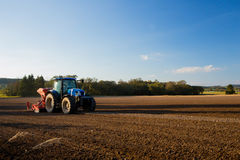 Tractor ploughs field. A blue tractor ploughs field Stock Photo