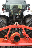Tractor with plow. Close-up of farming tractor with equipment in red color stock images