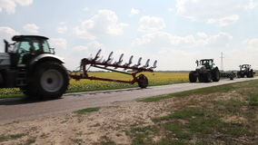 Tractor plow drill driving field of sunflowers Stock Photography