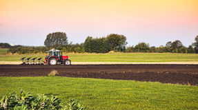 Tractor and plow in field Royalty Free Stock Image
