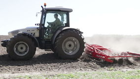 Tractor plow the field with dust stock video footage