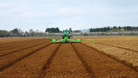 Tractor & Plow Tilling a Field Stock Image