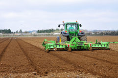 Tractor & Plow Tilling a Field Royalty Free Stock Photography