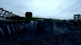 Tractor with a plow trailer plowing the field after sunset. A tractor with a plow trailer, lowering the millstone of the plow into the ground, plowing the field stock footage