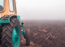 tractor on a plowed field. tractor at work. harvesting. late fall. foggy weather. early morning. royalty free stock photography