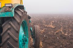 tractor on a plowed field. tractor at work. harvesting. late fall. foggy weather. early morning. stock photography