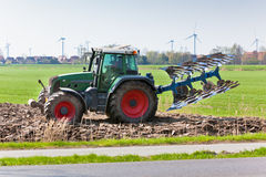 Tractor with plowes on the spring field. Stock Photo