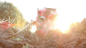 Tractor plowing the black earth plow field at sunset Stock Photos