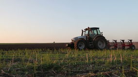 Tractor plowing the black earth plow field at sunset Royalty Free Stock Photo