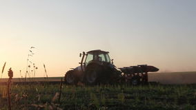Tractor plowing the black earth plow field at sunset Stock Image