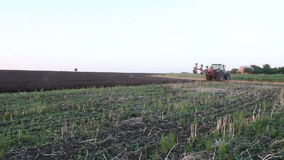 Tractor plowing the black earth plow field at sunset Royalty Free Stock Photography
