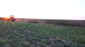 Tractor plowing the black earth plow field at sunset Stock Photo