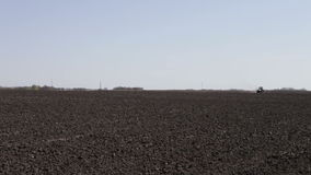 Tractor plowing black field boundless stock footage