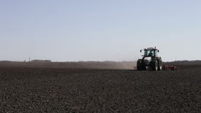 Tractor plowing black field boundless stock video