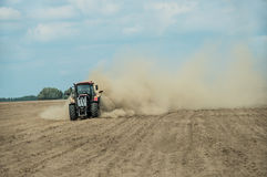 Tractor plowing dry farm land at autumn Stock Image
