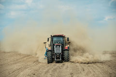 Tractor plowing dry farm land at autumn Stock Photos