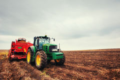 Tractor plowing farm field in preparation for spring planting Stock Images
