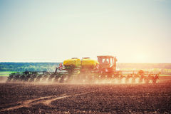 Tractor plowing farm field in preparation for spring planting Stock Photo