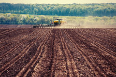 Tractor plowing farm field in preparation for spring planting Stock Photography
