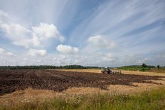 Tractor plowing farmland after harvest. In rural area. Brown, plowed soil in field. Cloudy blue sky as a background Stock Image