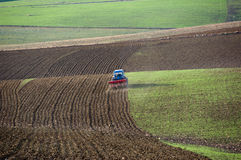 Tractor is plowing the field Stock Photos