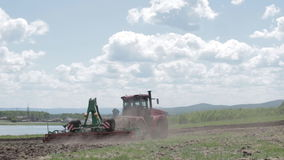 Tractor plowing a field on a beautiful day stock video footage