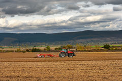 Tractor plowing a field at dusk Stock Photos