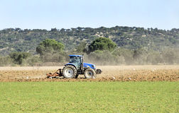 A tractor plowing a field Stock Photo