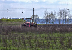 Tractor plowing a field in the spring. Red tractor on the background of forest and cloudy spring sky plowing a field Stock Images