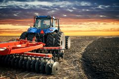 Tractor plowing field on sunset background. Tractor working on the farm, modern agricultural transport, farmer working in the field, tractor on a sunset Royalty Free Stock Photo