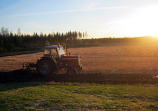 Tractor plowing a field at sunset Stock Photo