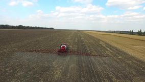 Tractor plowing the fields corn in spring. aerial