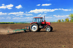 Tractor plowing the fields in early spring. Stock Photos