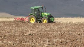 With tractor plowing fields stock video footage