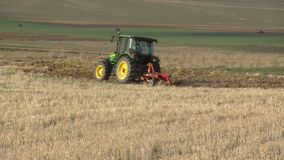 With tractor plowing fields Stock Image