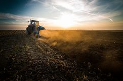 Tractor plowing fields -preparing land for sowing in autumn stock photos