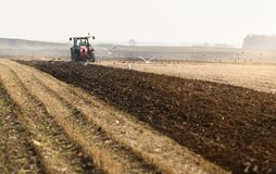 Tractor plowing fields  -preparing land for sowings Stock Photo