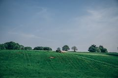 Tractor plowing the grass in the fields on a sunny day Stock Photography